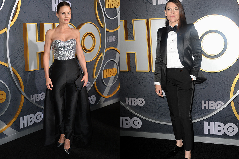 Jennifer Morrison wearing a black jumpsuit with a beaded bodice and clea DuVall wearing a black womens tuxedo with a black bow tie