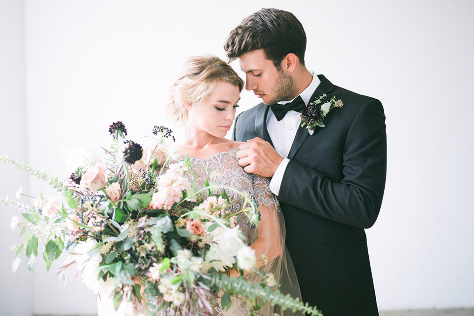 FD-Studios-Shoot-bride-and-groom-looking-down-bride-in-a-flowing-gown-with-intricate-neutral-beading-with-an-illusion-bodice-groom-in-a-traditional-black-tuxedo-with-a-black-bow-tie