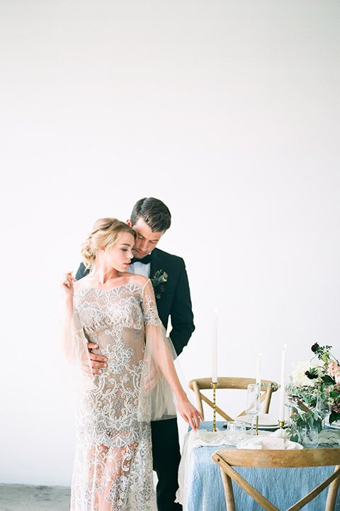 FD-Studios-Shoot-bride-and-groom-by-table-bride-in-a-flowing-gown-with-intricate-neutral-beading-with-an-illusion-bodice-groom-in-a-traditional-black-tuxedo-with-a-black-bow-tie