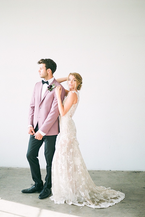 FD-Studios-Shoot-bride-and-groom-standing-by-windows-groom-in-pink-bride-in-a-flowing-gown-with-intricate-neutral-beading-with-an-illusion-bodice-groom-in-a-rose-pink-suit-with-a-black-bow-tie