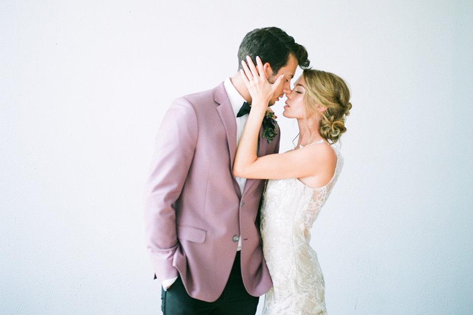 FD-Studios-Shoot-bride-holding-groom-face-bride-in-a-flowing-gown-with-intricate-neutral-beading-with-an-illusion-bodice-groom-in-a-rose-pink-suit-with-a-black-bow-tie