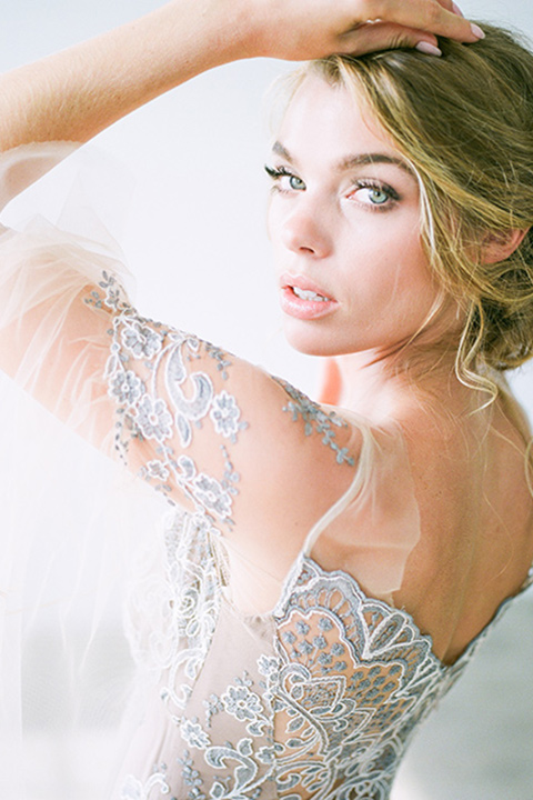 FD-Studios-Shoot-bride-looking-at-camera-in-a-flowing-gown-with-intricate-neutral-beading-with-an-illusion-bodice