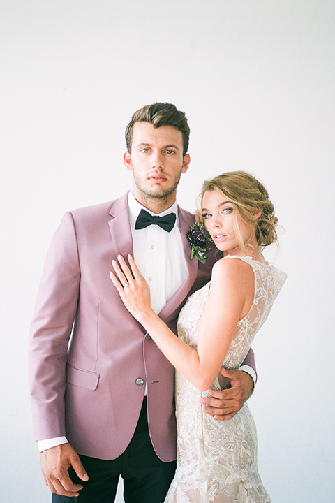FD-Studios-Shoot-couple-looking-at-camera-groom-in-pink-bride-in-a-flowing-gown-with-intricate-neutral-beading-with-an-illusion-bodice-groom-in-a-rose-pink-suit-with-a-black-bow-tie