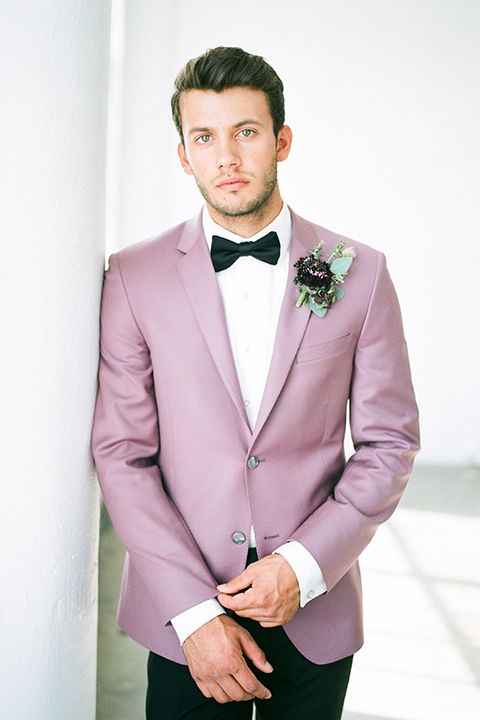 FD-Studios-Shoot-groom-in-pink-looking-at-camera-in-a-rose-pink-suit-with-a-black-bow-tie