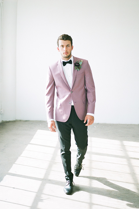 FD-Studios-Shoot-groom-in-pink-walking-towards-camera-in-a-rose-pink-suit-with-a-black-bow-tie
