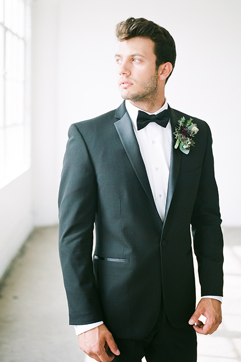 FD-Studios-Shoot-groom-looking-out-window-in-black-tuxedo-in-a-traditional-black-tuxedo-with-a-black-bow-tie
