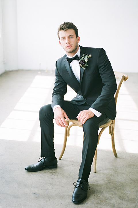 FD-Studios-Shoot-groom-sitting-in-chair-in-black-tux-in-a-traditional-black-tuxedo-with-a-black-bow-tie