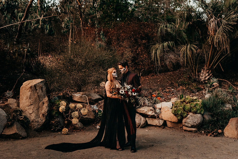 bride in a black gown with a black train and groom in a burgundy tuxedo with a black shirt both with their face painted in a skull pattern