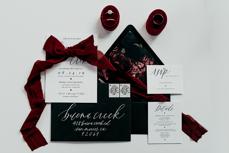 black invitations with white lettering and burgundy velvet ribbon