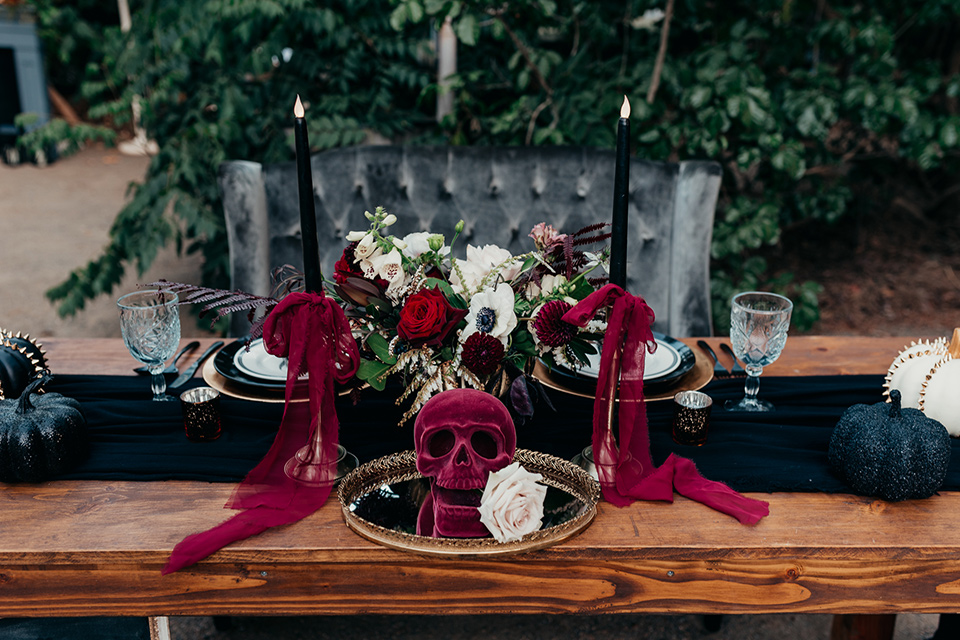 wooden table with black linens and tall black candles