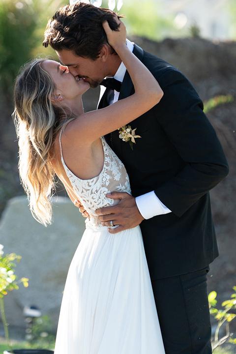 la-bonita-ranch-rustic-shoot-bride-and-groom-about-to-kiss-la-bonita-ranch-rustic-shoot-bridal-gown-with-a-high-neckline-and-a-nude-underlay-groom-in-a-navy-shawl-lapel-tuxedo-with-a-black-bowtie