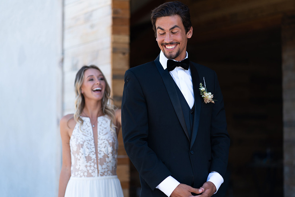 la-bonita-ranch-rustic-shoot-bride-and-groom-first-look-the-bride-in-a-white-bohemian-gown-with-a-nude-underlay-and-lace-detailing-groom-in-a-navy-shawl-lapel-tuxedo-with-a-black-bow-tie