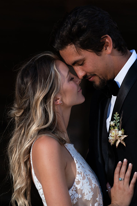 la-bonita-ranch-rustic-shoot-bride-and-groom-touching-heads-bridal-gown-with-a-high-neckline-and-a-nude-underlay-groom-in-a-navy-shawl-lapel-tuxedo-with-a-black-bowtie