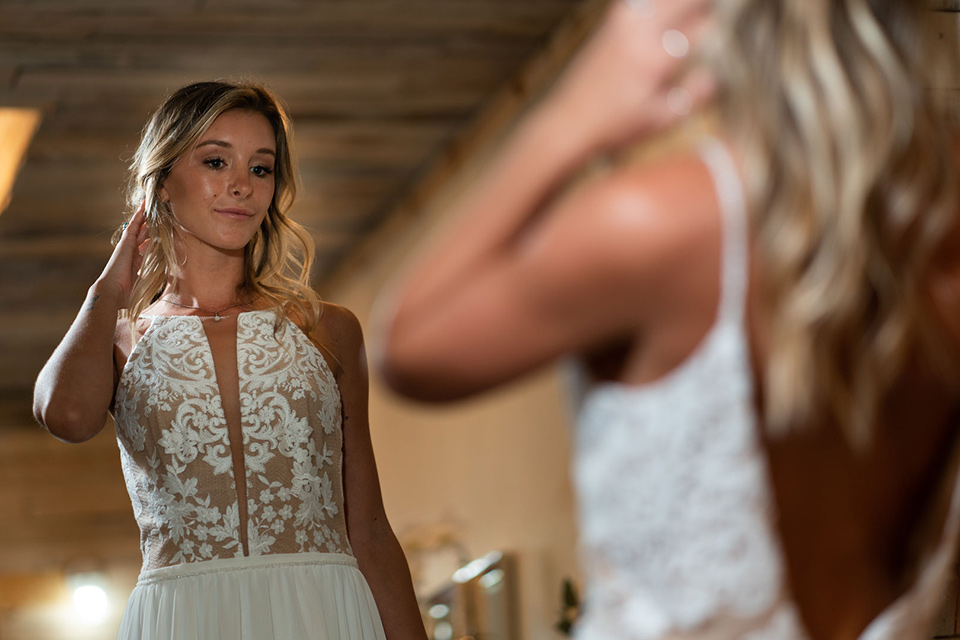la-bonita-ranch-rustic-shoot-bride-looking-in-the-mirror-the-bride-in-a-white-bohemian-gown-with-a-nude-underlay-and-lace-detailing