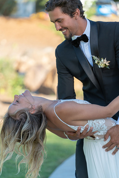 la-bonita-ranch-rustic-shoot-groom-dipping-bride-bride-in-a-white-bohemian-gown-with-a-high-neckline-with-a-lace-groom-in-a-navy-shawl-lapel-tuxedo-with-a-black-bowtie