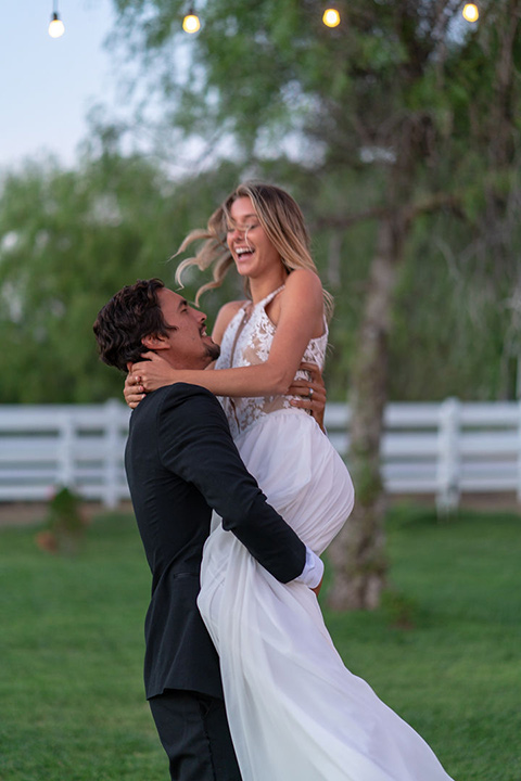 la-bonita-ranch-rustic-shoot-groom-holding-the-bride-up-smiling-bride-in-a-white-bohemian-gown-with-a-high-neckline-with-a-lace-groom-in-a-navy-shawl-lapel-tuxedo-with-a-black-bowtie