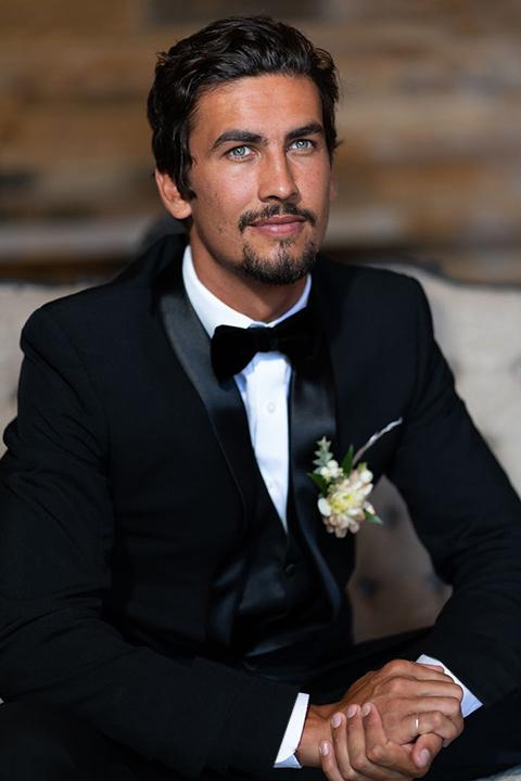 la-bonita-ranch-rustic-shoot-groom-sitting-looking-up-in-a-navy-shawl-lapel-tuxedo