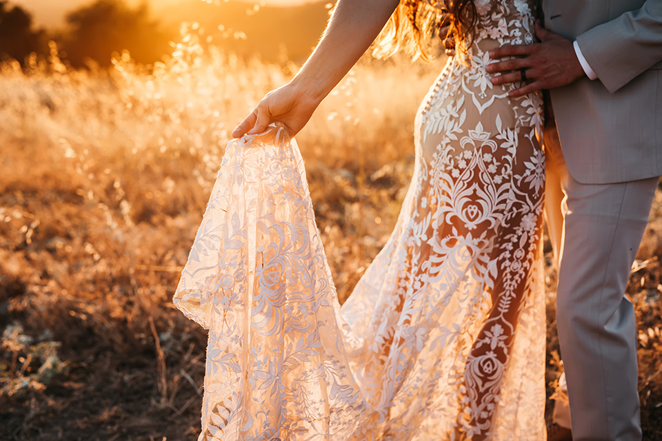 bride in a white bohemian style lace gown with a straps and a her hair in loose waves with the groom in a light grey suit