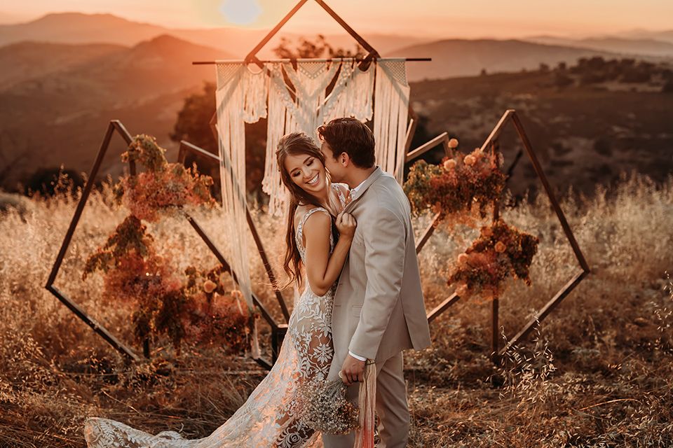 leave-her-wild-shoot-groom-kissing-bride-at-sunset