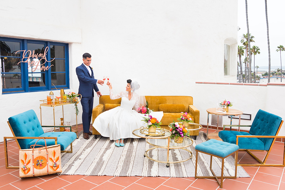 Ole-Hanson-Beach-Club-bride-and-groom-at-reception-area-with-mustard-and-blue-furniture-and-retro-style-rungs-and-decor