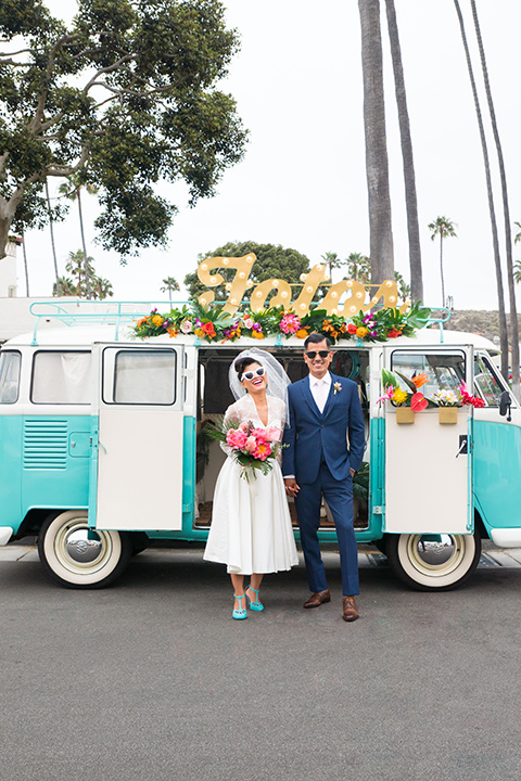 Ole-Hanson-Beach-Club-bride-and-groom-by-bus-the-bride-wore-a-tea-length-retro-inspired-gown-with-lace-sleeves-and-an-elbow-length-veil-the-groom-wore-a-dark-blue-suit-with-a-light-pink-long-tie-and-brown-shoes