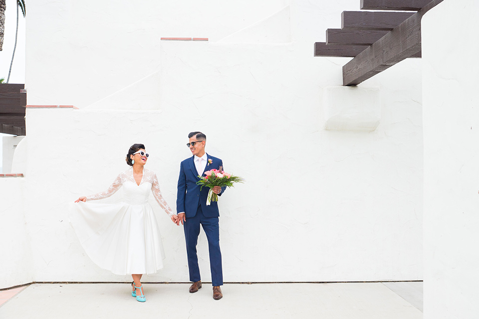 Ole-Hanson-Beach-Club-bride-and-groom-by-white-wall-the-bride-wore-a-tea-length-gown-with-lace-sleeves-and-an-elbow-length-veil-the-groom-wore-a-dark-navy-blue-suit-with-a-blush-pink-long-tie-and-brown-shoes