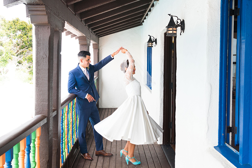 Ole-Hanson-Beach-Club-bride-and-groom-dancing-the-bride-wore-a-tea-length-gown-with-lace-sleeves-and-an-elbow-length-veil-and-team-retro-heels-the-groom-wore-a-dark-navy-blue-suit-with-a-blush-pink-long-tie-and-brown-shoes