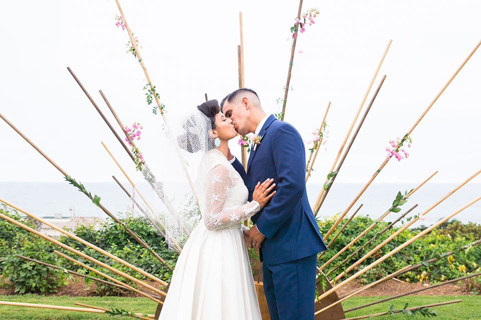 Ole-Hanson-Beach-Club-bride-and-groom-kissing-at-ceremony-the-bride-wore-a-tea-length-gown-with-lace-sleeves-and-an-elbow-length-veil-and-team-retro-heels-the-groom-wore-a-dark-navy-blue-suit-with-a-blush-pink-long-tie-and-brown-shoes