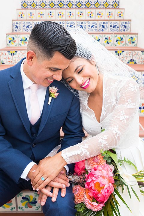 Ole-Hanson-Beach-Club-bride-and-groom-on-steps-the-bride-wore-a-tea-length-retro-inspired-gown-with-lace-sleeves-and-an-elbow-length-veil-and-teal-blue-heels-the-groom-wore-a-dark-blue-suit-with-a-light-pink-long-tie-and-brown-shoes