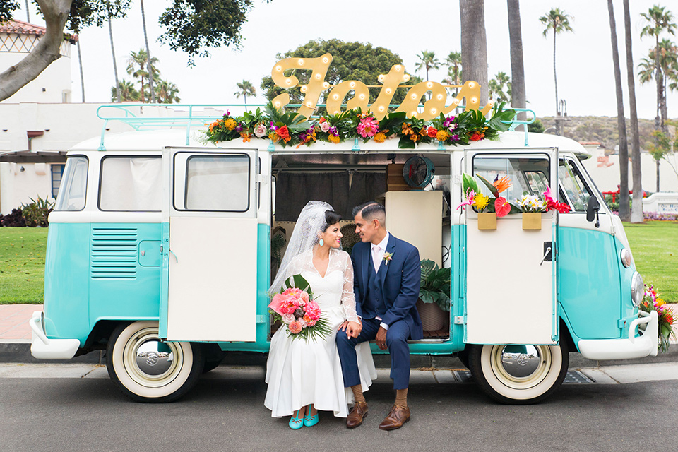 Ole-Hanson-Beach-Club-bride-and-groom-sitting-in-bus-the-bride-wore-a-tea-length-gown-with-lace-sleeves-and-an-elbow-length-veil-and-team-retro-heels-the-groom-wore-a-dark-navy-blue-suit-with-a-blush-pink-long-tie-and-brown-shoes