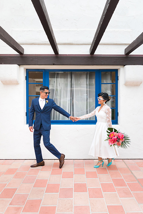 Ole-Hanson-Beach-Club-bride-and-groom-walking-the-bride-wore-a-tea-length-gown-with-lace-sleeves-and-teal-retro-inspired-heels-the-groom-wore-a-dark-blue-suit-with-a-light-pink-long-tie-and-brown-shoes