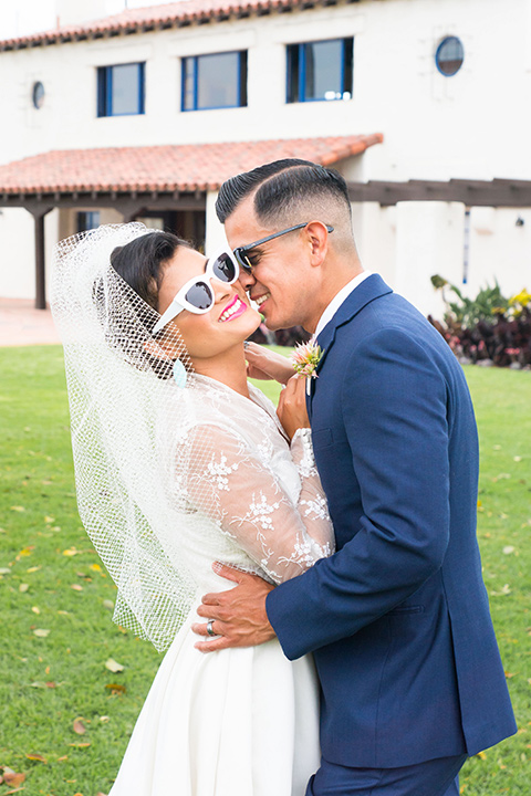 Ole-Hanson-Beach-Club-bride-and-groom-with-sunglasses-the-bride-wore-a-tea-length-retro-inspired-gown-with-lace-sleeves-and-an-elbow-length-veil-and-teal-blue-heels-the-groom-wore-a-dark-blue-suit-with-a-light-pink-long-tie-and-brown-shoes