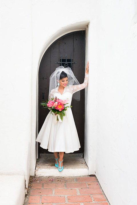 Ole-Hanson-Beach-Club-bride-looking-at-the-camera-in-a-tea-length-retro-inspired-gown-with-lace-sleeves-and-an-elbow-length-veil-and-teal-blue