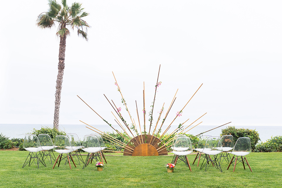Ole-Hanson-Beach-Club-ceremony-space-with-a-geometric-sun-like-décor-where-the-ceremony-would-take-place-and-white-and-wood-chairs-on-a-green-lawn