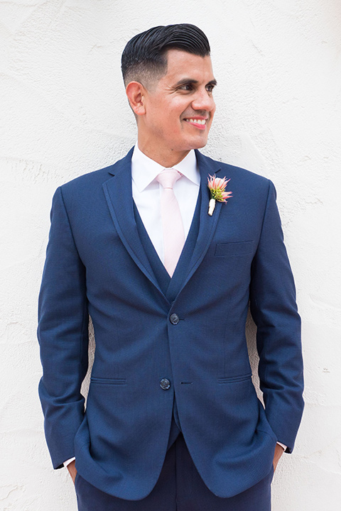 Ole-Hanson-Beach-Club-groom-by-white-wall-in-a-dark-blue-suit-with-a-light-pink-long-tie-and-brown-shoes