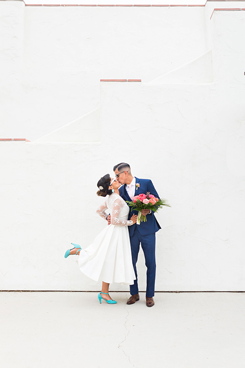 Ole-Hanson-Beach-Club-groom-kissing-bride-bride-kciking-her-heel-up-the-bride-wore-a-tea-length-gown-with-lace-sleeves-and-teal-retro-inspired-heels-the-groom-wore-a-dark-blue-suit-with-a-light-pink-long-tie-and-brown-shoes