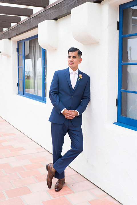 Ole-Hanson-Beach-Club-groom-standing-against-the-wall-in-a-dark-blue-suit-with-a-light-pink-long-tie-and-brown-shoes