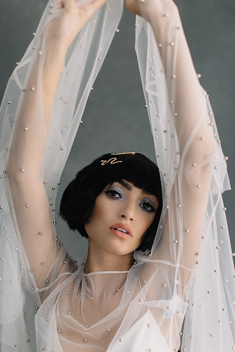 Modern-Mystical-Styled-shoot-at-the-york-bride-with-hands-overhead-in-a-short-sheer-dress-with-a-silk-underlay