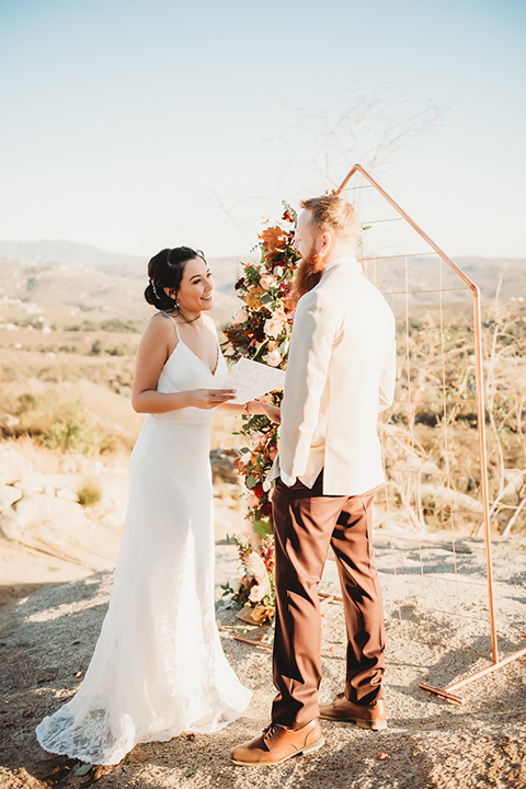 Moonflower-Ranch-Shoot-bride-and-groom-at-ceremony-bride-in-a-lace-form-fitting-gown-with-straps-and-v-neck-line-groom-in-a-tan-suit-jacket-with-burgundy-pants-and-floral-necktie