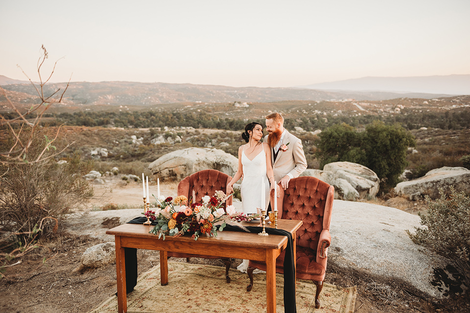 Moonflower-Ranch-Shoot-bride-and-groom-by-table-bride-in-a-form-fitting-lace-gown-with-straps-groom-in-a-tan-jacket-burgundy-pants-and-a-white-floral-long-tie