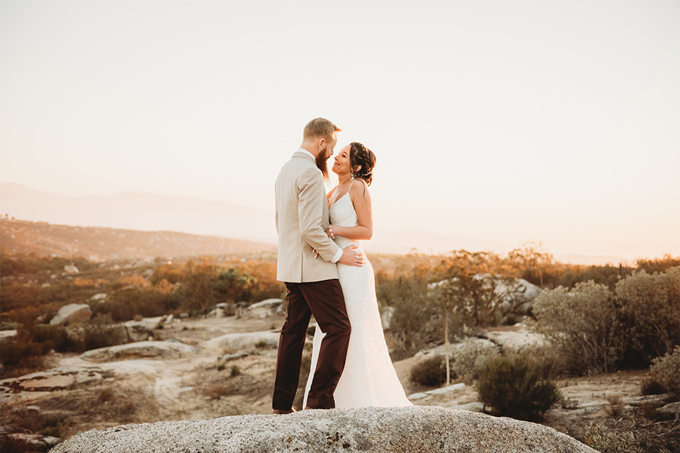 Moonflower-Ranch-Shoot-bride-and-groom-embrace-on-mountain-bride-in-a-form-fitting-lace-gown-with-straps-groom-in-a-tan-jacket-burgundy-pants-and-a-white-floral-long-tie