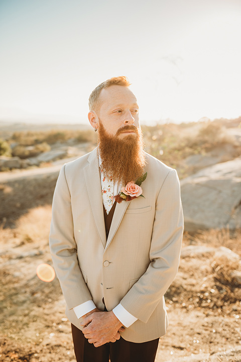Moonflower-Ranch-Shoot-groom-crossing-hands-close-up-in-a-tan-suit-jacket-with-burgundy-pants-and-floral-necktie