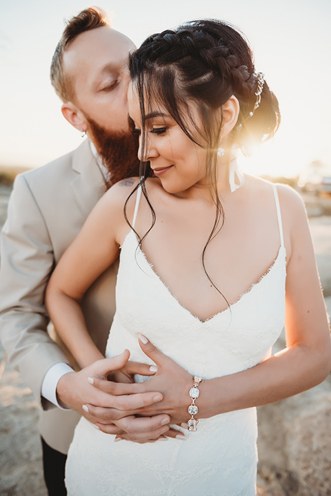 Moonflower-Ranch-Shoot-groom-holding-bride-from-behind-bride-in-a-lace-form-fitting-gown-with-straps-and-v-neck-line-groom-in-a-tan-suit-jacket-with-burgundy-pants-and-floral-necktie