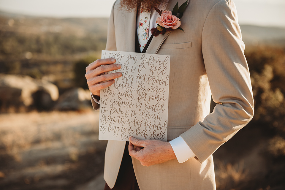 Moonflower-Ranch-Shoot-groom-holding-vows-in-a-tan-jacket-burgundy-pants-and-a-white-floral-long-tie