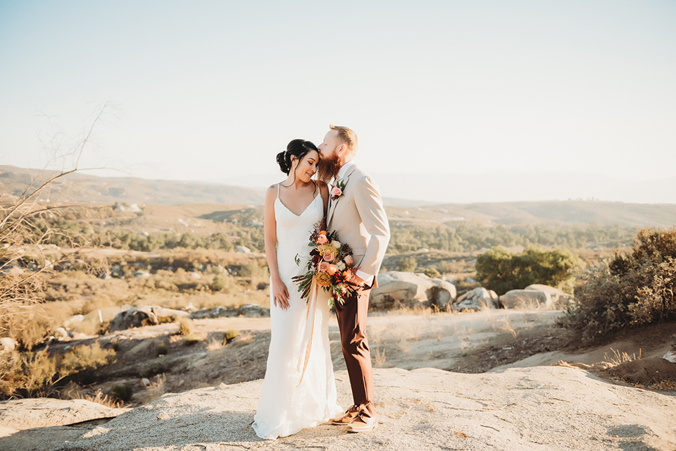Moonflower-Ranch-Shoot-groom-kissing-bride-on-forehead-bride-in-a-form-fitting-lace-gown-with-straps-groom-in-a-tan-jacket-burgundy-pants-and-a-white-floral-long-tie