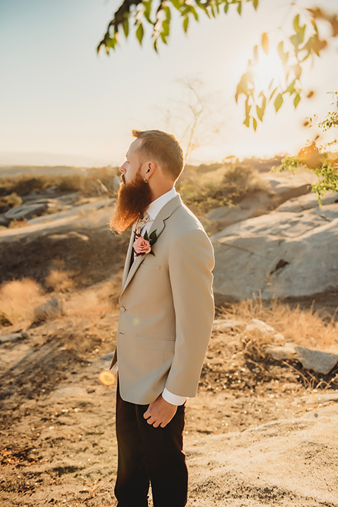 Moonflower-Ranch-Shoot-groom-looking-to-the-side-in-a-tan-suit-jacket-with-burgundy-pants-and-floral-necktie