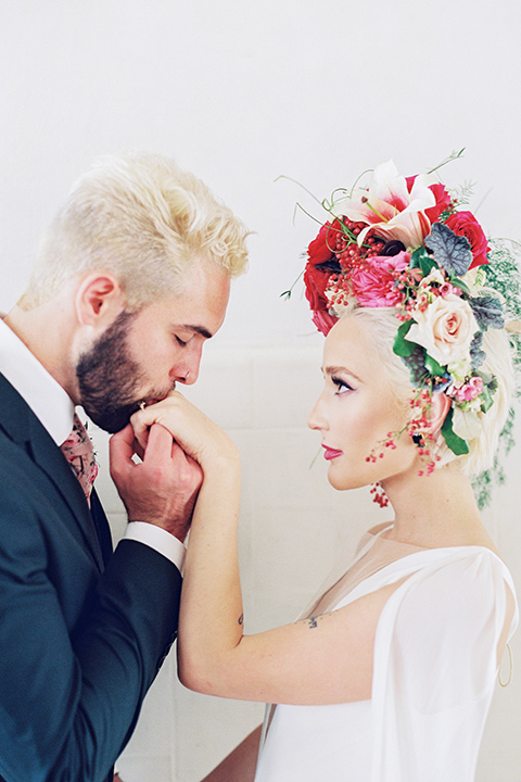 II-Mercato-in-New-Orleans-groom-kissing-brides-hand-bride-in-a-fitting-minimalistic-dress-with-a-high-neckline-and-floral-crown-groom-in-a-green-suit-with-brown-shoes-and-floral-long-tie