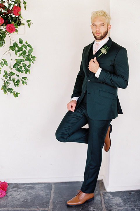 II-Mercato-in-New-Orleans-groom-standing-alone-groom-in-a-green-suit-with-brown-shoes-and-floral-long-tie