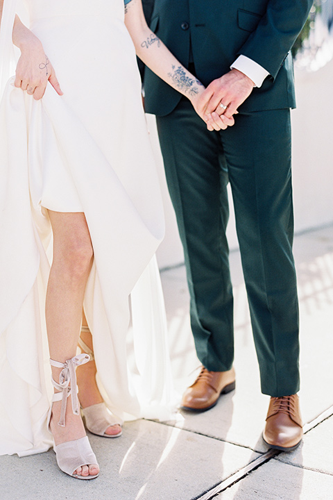 II-Mercato-in-New-Orleans-shoes-bride-in-a-fitting-minimalistic-dress-with-a-high-neckline-and-floral-crown-groom-in-a-green-suit-with-brown-shoes-and-floral-long-tie
