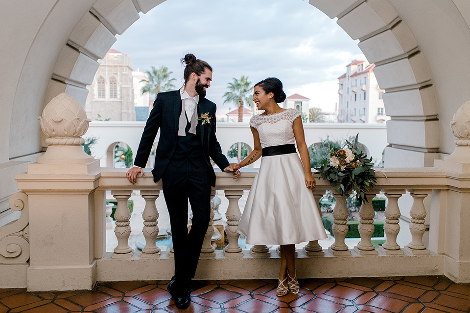 Pasadena-city-hall-styled-shoot-bride-and-groom-holding-hands-under-archway-bride-in-a-short-dress-with-cap-sleeves-groom-in-a-navy-shawl-lapel-tuxedo-with-an-undone-light-blue-bow-tie